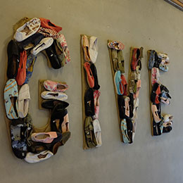 Sign of the word 'GIVE' composed of TOMS shoes hangs on a wall.