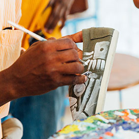 Haiti-based artist hand paints a pair of TOMS classics through the Haiti Artist Collective.