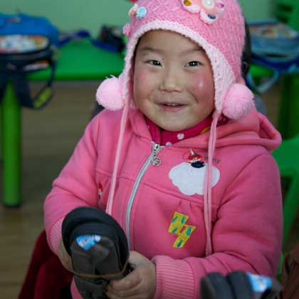 Young Chinese girl receives a pair of new shoes.