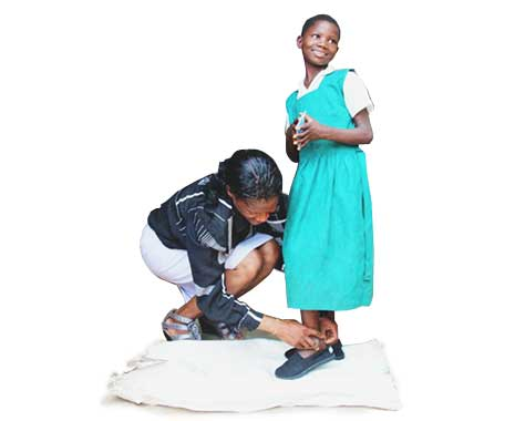 Young girl receives the gift of new shoes.